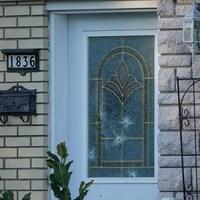 Plusieurs impacts de balles sur la porte d'entrée d'une résidence.