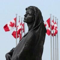 Visage de la statue Veritas entourée de drapeaux du Canada en mai 2018 à Ottawa.