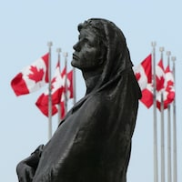 Une image de la statue Veritas devant l'édifice de la Cour suprême du Canada. L'œuvre incarne la vérité.
