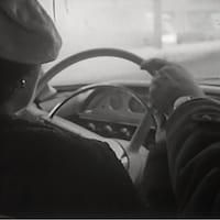 Femme vue de dos qui conduit et moniteur de conduite près d'elle avec une main sur le volant.