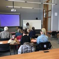 Des jeunes et moins jeunes suivent un cours dans une salle de classe d'université.