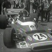 Un pilote de formule 1 est assis dans une voiture de course à l'arrêt et est entouré de jeunes.