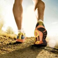 Un homme court dans un sentier, chaussé d'espadrilles jaune, orange et noir.