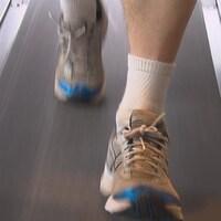 Les pieds d'un homme qui court sur un tapis de course