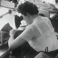 Une couturière courbée sur sa machine à coudre dans une manufacture.