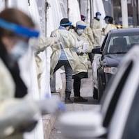 Des automobilistes passent devant du personnel médical pour subir un test de dépistage.