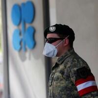 Un soldat autrichien se tient à côté du logo de l'Organisation des pays exportateurs de pétrole (OPEP) devant le siège de l'organisation à Vienne.