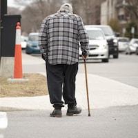 Un homme âgé marche sur le trottoir avec une canne, dans une rue où passent des voitures.