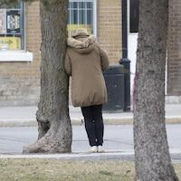 Une personne seule est appuyée sur un arbre.