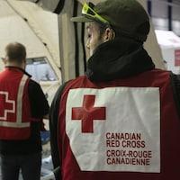 Un employé portant un dossard avec le sigle de la Croix-Rouge.