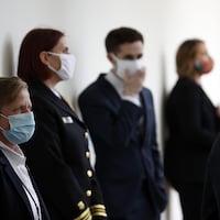 Des employés de la Maison-Blanche portent un masque lors de la conférence de presse de Donald Trump.