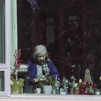 Une personne est photographiée à travers une fenêtre au centre de soins longue durée Lynn Valley à North Vancouver, en Colombie-Britannique, le lundi 9 mars 2020.
