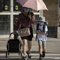 Une mère et son enfant portant un masque sur le trottoir.