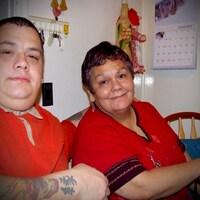 Un homme pose à gauche de sa mère âgée dans une cuisine.