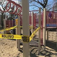 Une banderole jaune autour d'une structure de jeux dans un parc.