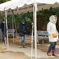 Plusieurs personnes portant des masques font la queue à l'extérieur.