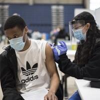 Gina Mikhail administre une dose d'un vaccin contre la COVID-19 à Mathew Derrick-Huie à Mississauga.