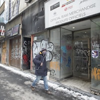Un homme marche devant des commerces vandalisés et abandonnés.