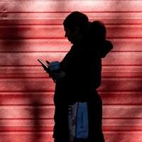 Une femme marche sur un trottoir avec son téléphone portable en main.
