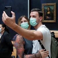 Des visiteuses devant La Joconde et un couple portant un masque au musée du Louvre faisant un égoportrait.