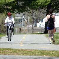 Une dame à vélo et une autre à la course se croisent sur une piste cyclable tout en respectant la distanciation physique.