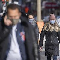 Des passants portent des masques faciaux.