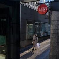 Une femme marche dans la rue avec des sacs à la main.