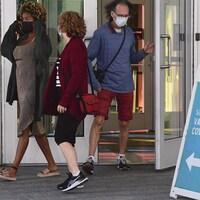 Un homme et deux femmes portant un masque de protection près d'un centre de vaccination à Montréal.