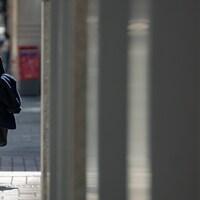 Une femme marche dans la rue avec un masque au visage.