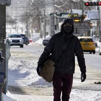 Une personne marche dans la rue en hiver, avec un masque au visage.