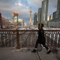 Une Torontoise marche dans la rue avec un masque; la Tour CN est en arrière-plan.
