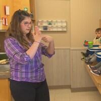 Une éducatrice pointe l'index de sa main gauche dans la paume de sa main droite.