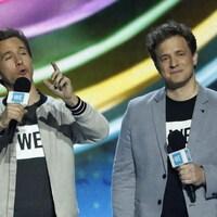 Craig et Marc Kielburger sur scène tiennent des micros.