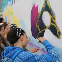 Des jeunes en train de peindre une murale.