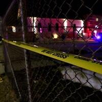 Un policier pose un ruban jaune sur une clôture pour interdire l'accès à la zone ainsi délimitée.