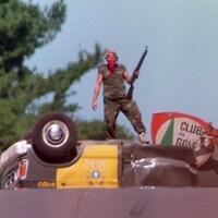 Un Mohawk se tient debout sur une voiture de police renversée.