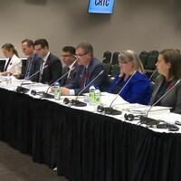 Les représentants de BCE Inc, assis à une table dans une salle de conférence