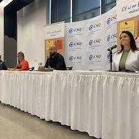 Deux hommes et deux femmes assis à une table derrière des microphones lors d'une conférence de presse.