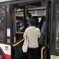Des dizaines de navetteurs se pressent dans un autobus de la CTT dans le nord-ouest de Toronto pendant l'heure de pointe du matin.