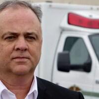 Michel Chrétien devant une ambulance.