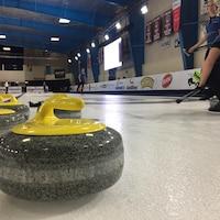 La caméra fait un gros plan sur les instruments de curling, avec des joueuses en arrière plan sur la patinoire.