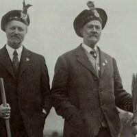 Deux hommes portant le costume traditionnel écossais et tenant chacun un balai.
