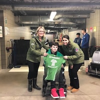 Un adolescent en fauteuil roulant entouré de deux curleuses se fait offrir un chandail de curling.