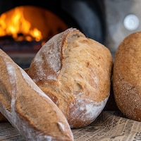 Des pains devant un four à bois.