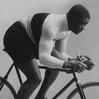 Sur cette photo d'archives, on voit le cycliste Major Taylor sur son vélo, de profil, prenant la pose comme s'il était en action.