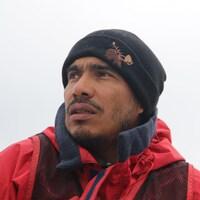Photo de Dario Izaguirre qui porte une tuque et un manteau et regarde au loin.