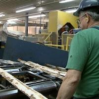 Un travailleur dirige des morceaux d'arbres dans de la machinerie de l'usine.