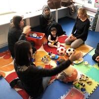 Des éducatrices en garderies assises dans une aire de jeu.