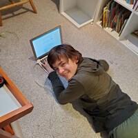 Daniel Harvey souriant est allongé sur un tapis beige devant un ordinateur portable.