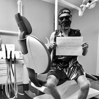 Un homme pose sur une chaise de dentiste avec une pancarte sur laquelle on peut lire : « Chirurgien-dentiste solidaire travail impossible sans protections ».